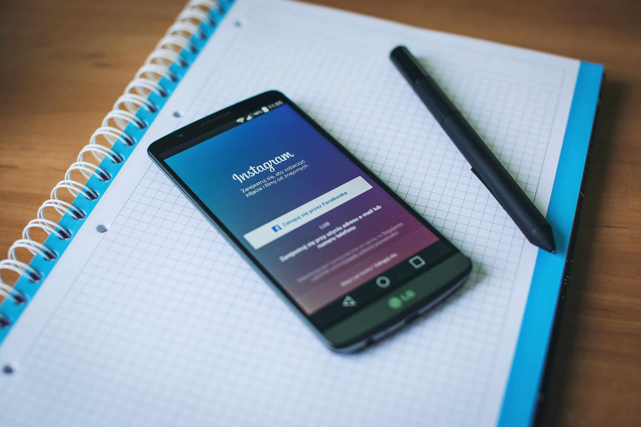 Facebook login page shown on a smartphone that is resting on a notebook and next to a pen