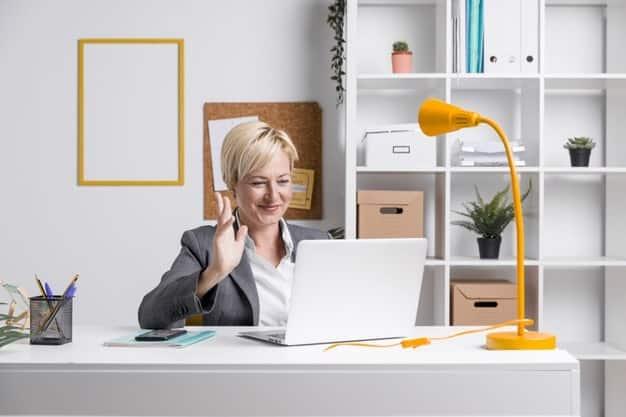 woman waving at the laptop