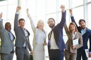 corporate team raising hands and celebrating success